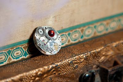 upcycled steampunk pin with watch parts and red stone