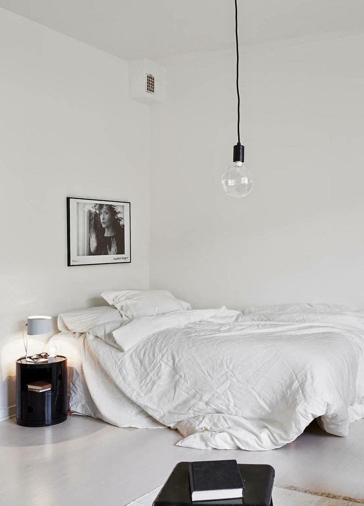 simple scandi inspired white and black bedroom with messy crumpled linen bed