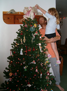 Daddy lifting Rachel to put on Christmas tree topper