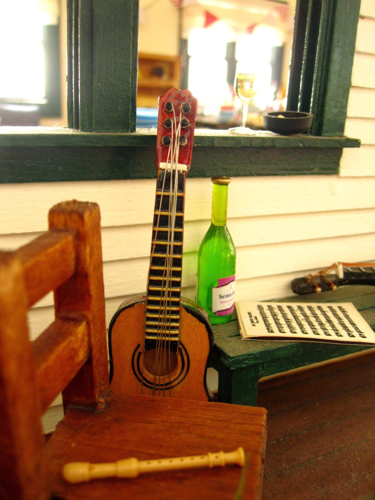 A miniature dolls' house veranda, with seating, a bottle and glass of wine, a recorder, guitar, ukulele and sheet of music.