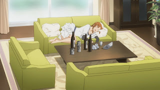 Kozue śpi na kanapie, przed nią stół z pustymi butelkami po alkoholu