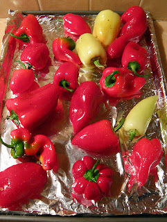 Many shapes and sizes of red and yellow peppers on baking sheet