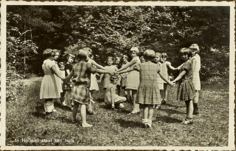 girls standing in a ring in a garden playing a game