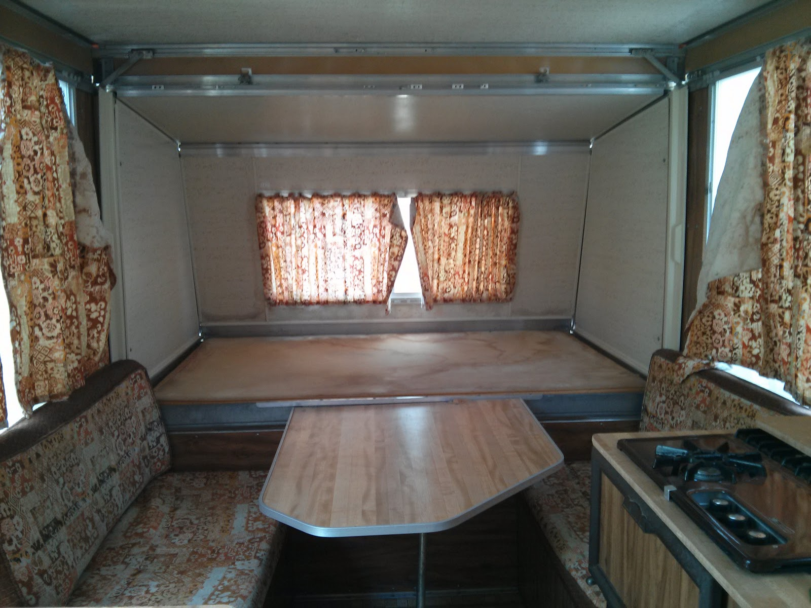 1976 Apache Mesa camper interior with original brown upholstery and curtains