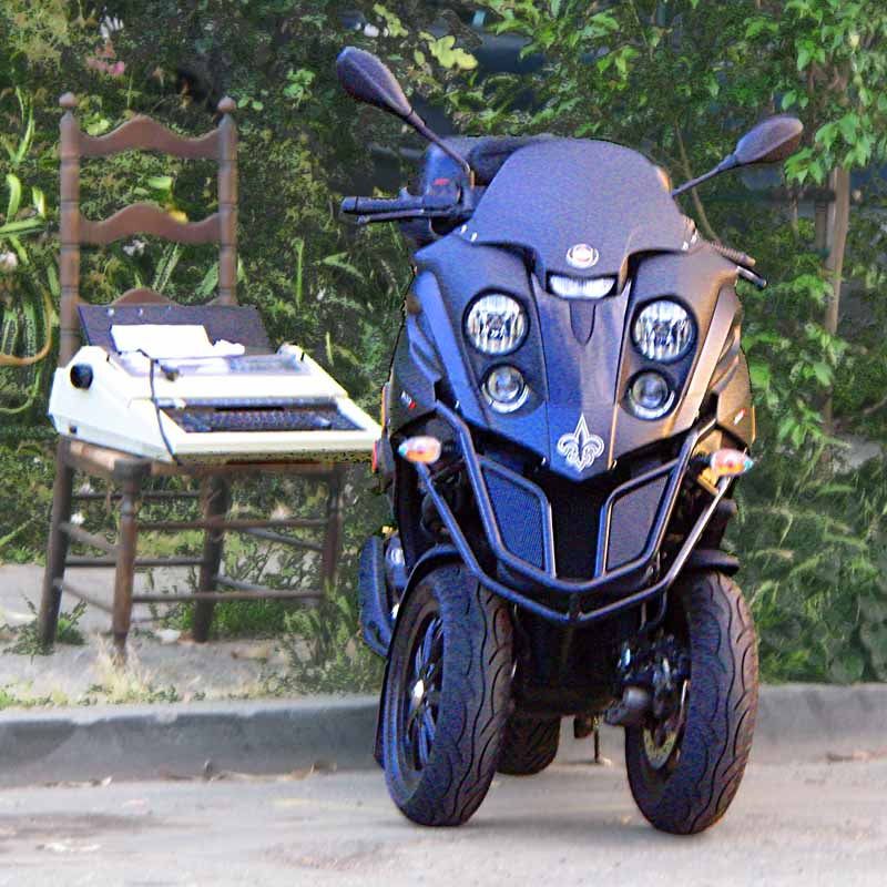 4-eyed 3-wheel motorcycle looks like Predator or Darth Vader and has an electric typewriter sitting on an old wooden chair as a sidekick (c) David Ocker