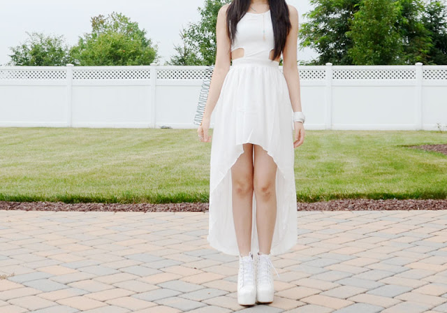 Front view of this white summer outfit, with the high-low cutout dress from WalkTrendy, along with bohemian-chic jewelry and spiked white platform booties.