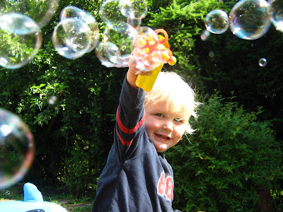 boy with long blond hair having fun with bubbles outside