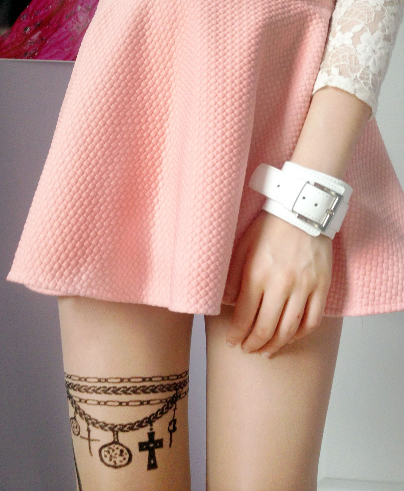 Close-up of the pure color elastic waist mini skater skirt in pastel/pale pink and the tattoo chain & wings tights from Chicnova!