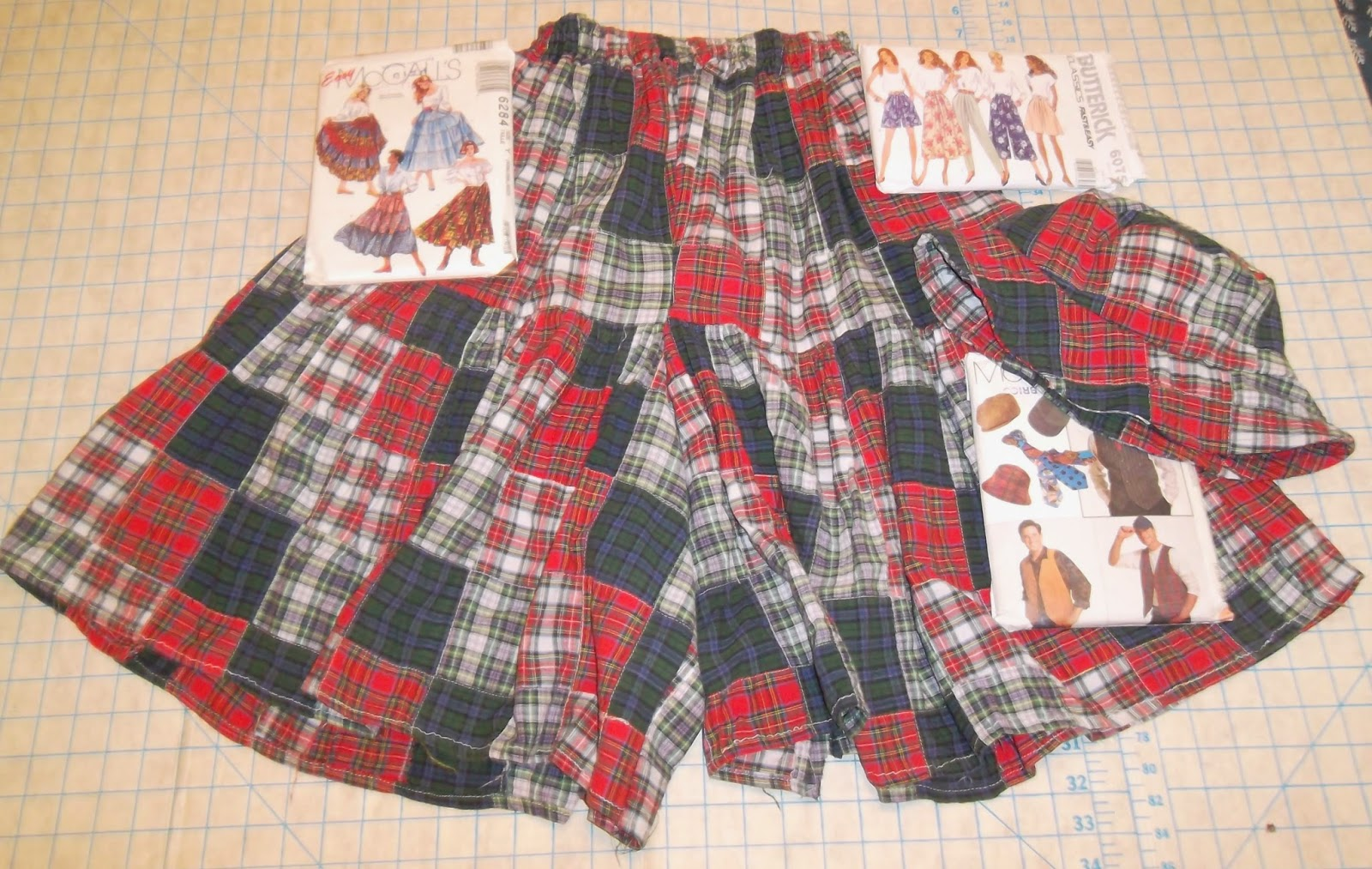 Woman's divided skirt and hat, made from fabric that consists of piecework squares in four plaid designs: dark red, blue and green, red on white and blue and green on white.  In upper left, a sewing pattern for a three-paneled long skirt is laid on top of the garment. In upper right, a pattern for the divided skirt. And in lower right, a sewing pattern for the hat.