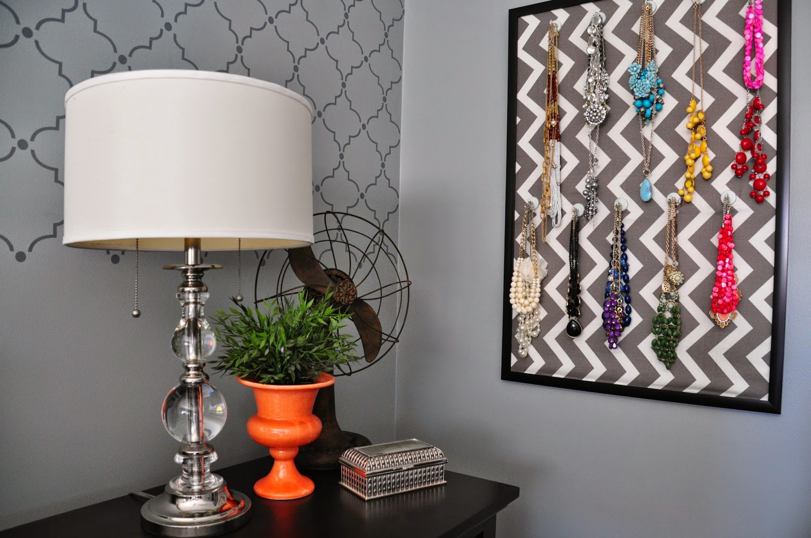Pops of orange on the nightstand of this master bedroom along with the fun necklace organizer :: OrganizingMadeFun.com