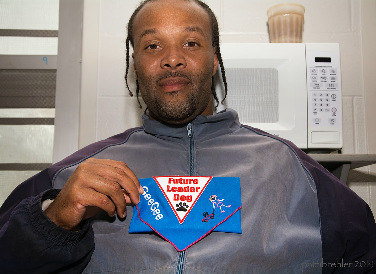 A head and shoulder shot of an African American man wearing a grey and blue jacket. He is holding a folded blue Future Leader Dog bandana at his chest with his right hand.