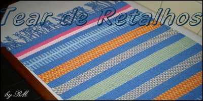 Tecelagem manual com listras coloridas, predominando o azul com destaque avermelhado sugerindo a luz solar