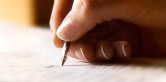 Mano escribiendo en hoja de papel