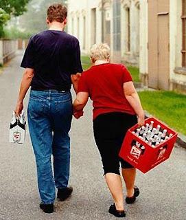 Mulher carrega grade - Homem carrega garrafinhas