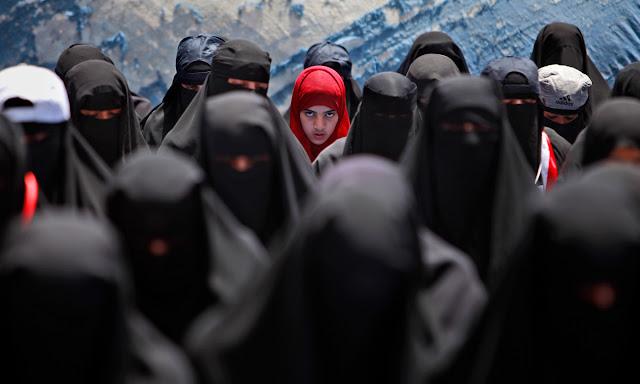 Kvinde med rødt tørklæde kigger op under bøn ved protest demonstration mod Yemens præsident