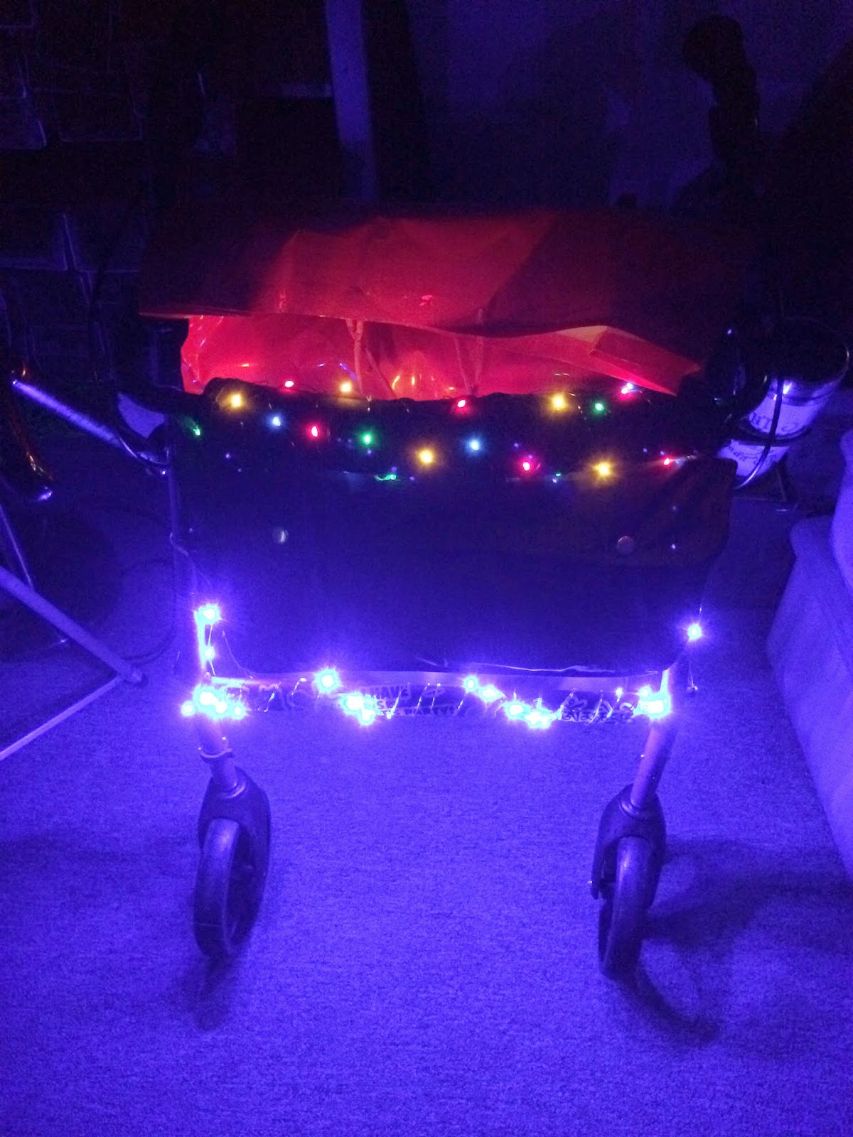 Photograph: A close-up of the font of a rollator walker. Wrapped around the front bar is a string of lights that are shining bright blue. Wrapped around the top bar is a sting of Christmas lights in red, green, blue, and yellow that are reflecting off of a red bag.