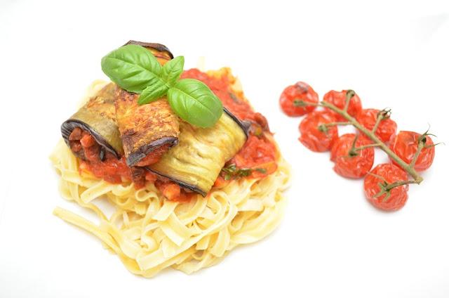 Foto av en liten porsjon pasta med tomatsaus på og aubergineruller på toppen. Det hele er pyntet med et basilikumblad. Bakgrunnen er helt hvit. Til høyre for pastaporsjonen er en lang tomatstilk med syv ovnsbakte cherrytomater festet til seg.