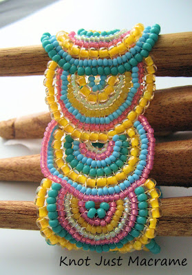 Close up of bead weaving bracelet in apricot and teal and other spring colors