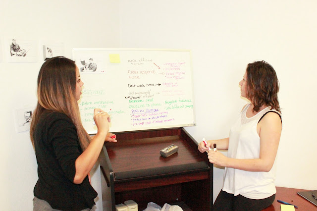 Two women think of ideas and writing them down on a whiteboard