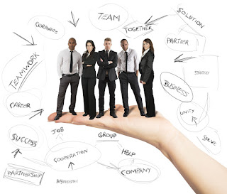 5 miniature business people stand on a giant hand and are surrounded by words denoting team success