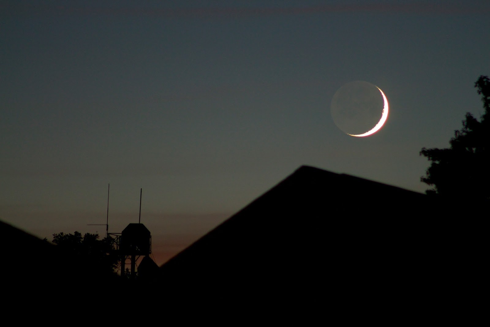 crescent moonset over roof