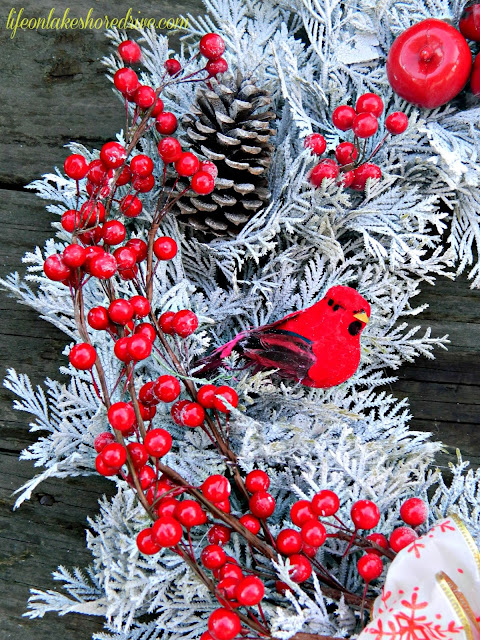 "alt=""Winter red and white wreath with cardinals berries and pine cones"""