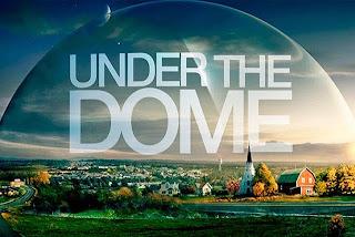"""Kleine Stadt in Flachland unter einer sichtbaren Kuppel, der Schriftzug """"UNDER THE DOME"""""""