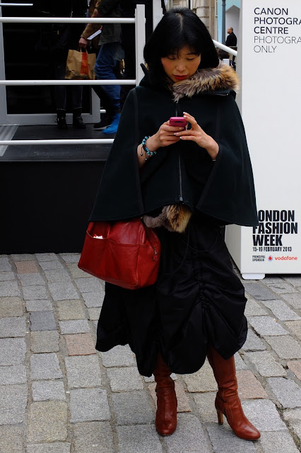 girl wearing cape and red bag texting at the LFW AW13