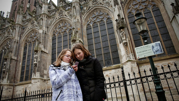 asmijn Aartsen, left, and Roos Verheijen, both 13, called the number on a sign outside St. John the Evangelist Cathedral in 's Hertogenbosch.