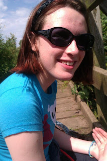A photo of me on a wooden bridge wearing a blue t-shirt and with my just above the shoulder browny red hair and big dark sunglasses.