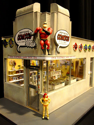Front view of a modern dolls' house miniature comic book shop in an art deco building