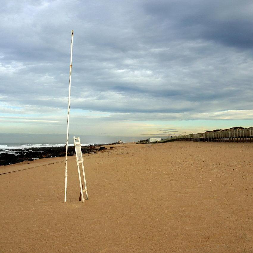 Foto da praia deserta, com a haste da bandeira em primeiro plano, o passadiço à direita e a Capela do Senhor da pedra ao longe. Céu nublado.