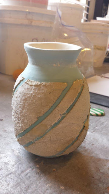 Ceramic hand thrown pottery vase prepared with sacrificial slip for naked raku firing.