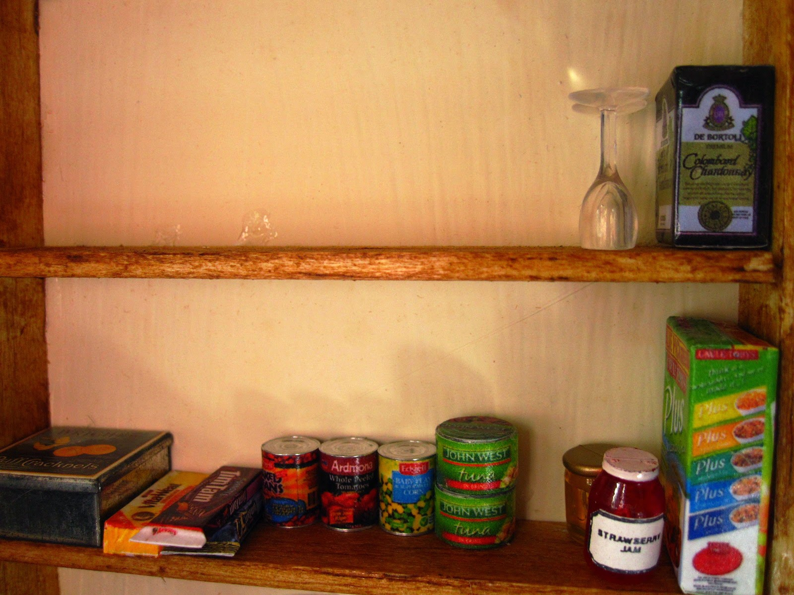 A selection of modern miniature groceries arranged on shelves.