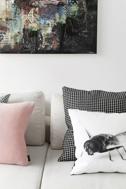 close up of a living room by bo bedre with a light gray sofa with black and white check pillows, a pink pillow and a white pillow with a large fly printed on it