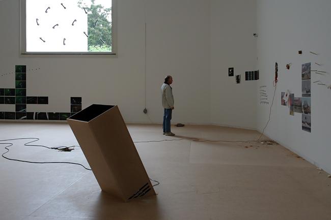 Sala de exposição com uma instalação no centro, janela ao fundo com elementos colados e quadros na direita a serem observados por um espectador