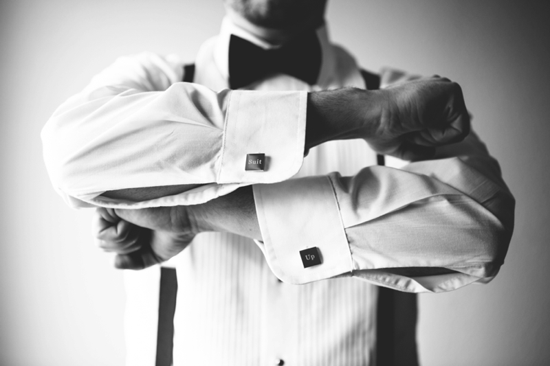 the groom wearing suit up cuff links
