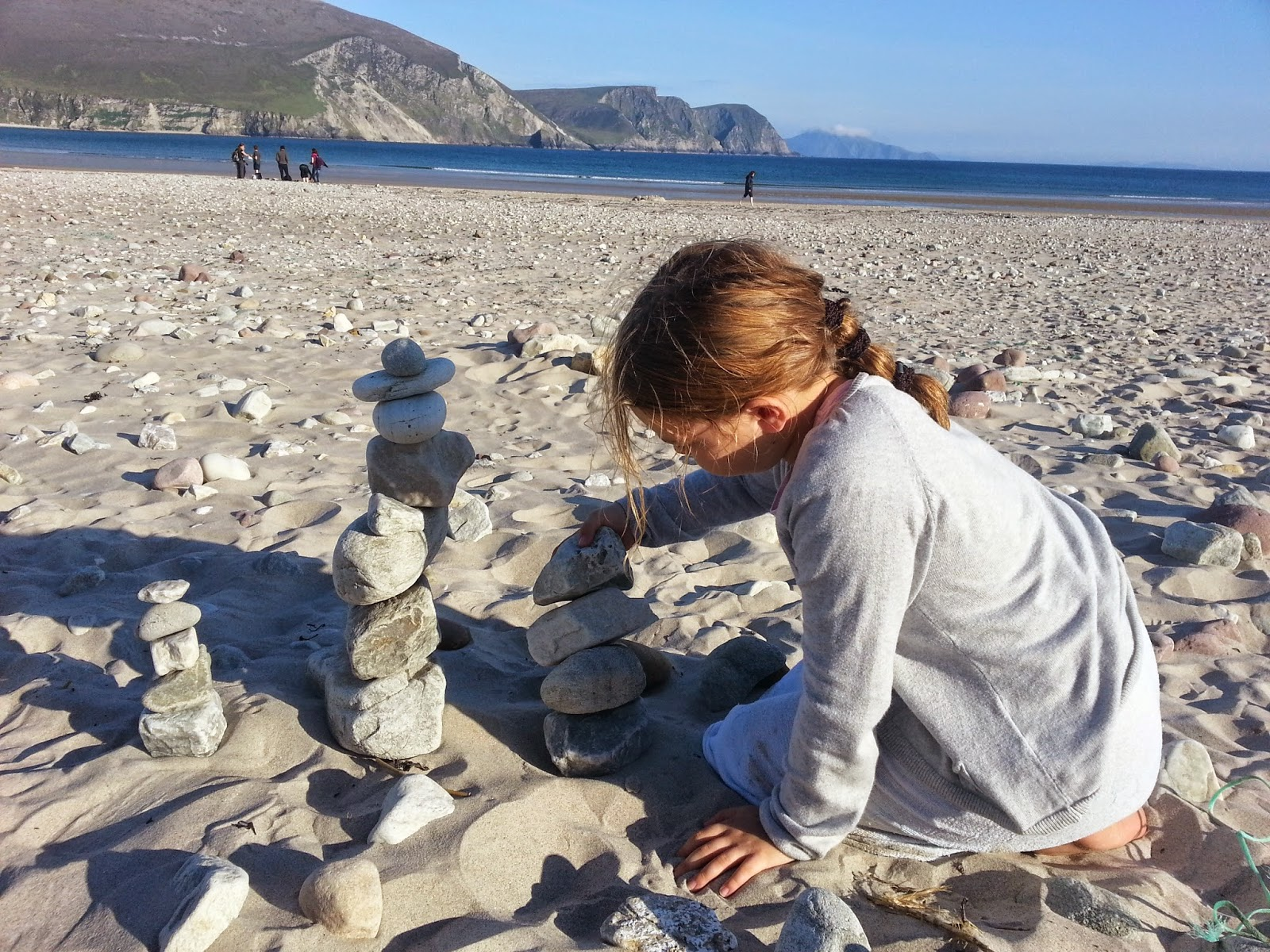 young girl making stone sculptures on Keel Beach