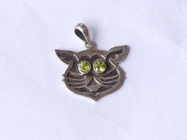 Silver cat pendant with peridot eyes