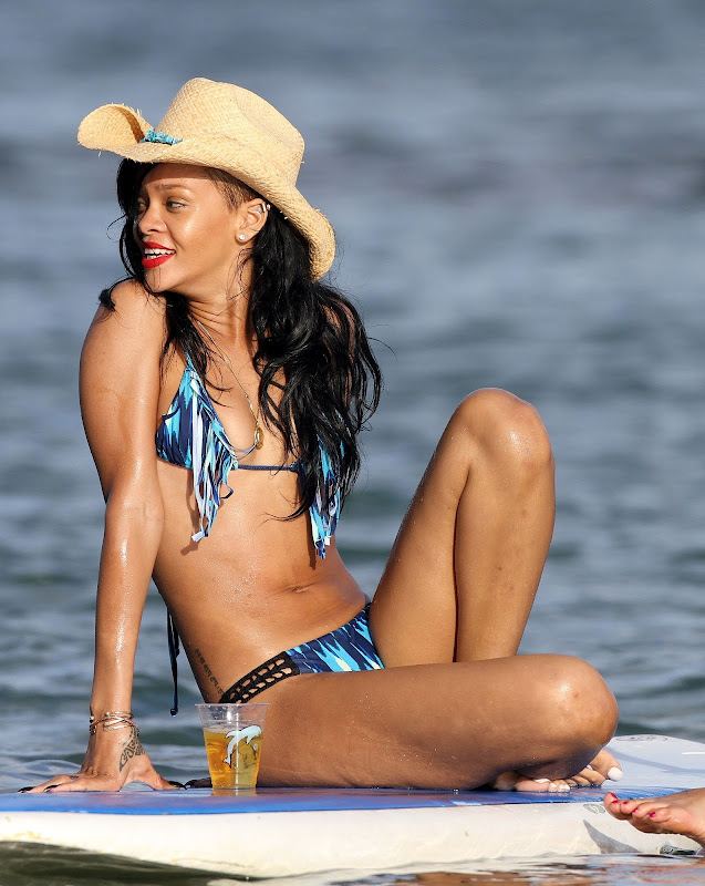 Rihanna having a dring on a paddle board In Hawaii