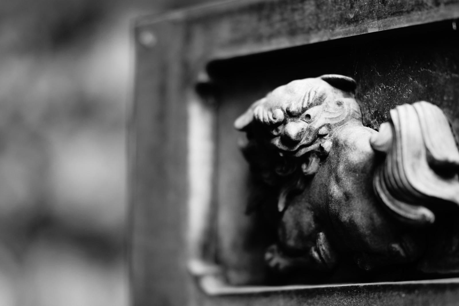 灯篭に彫られた狛犬の装飾の写真