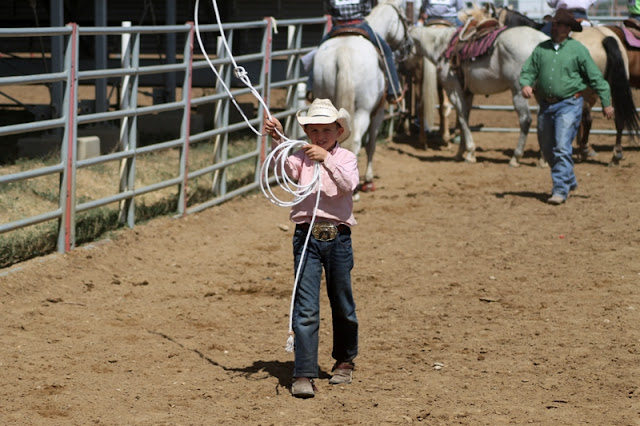 a young cowboy practices his roping technique