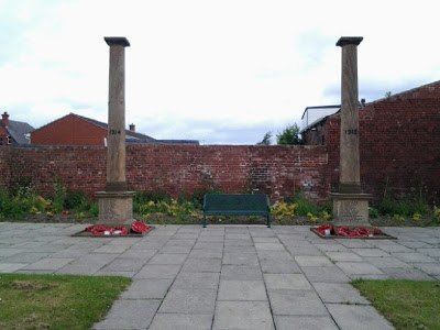 Two pillars in a walled garden, a bench between.  The bases of the pillars are inscribed with names and there are poppy wreaths around the bottoms of the pillars.