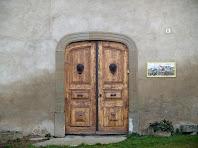 Detall del portal d'accés amb la llinda d'arc rebaixat, i picaportes de ferro imitant lleons