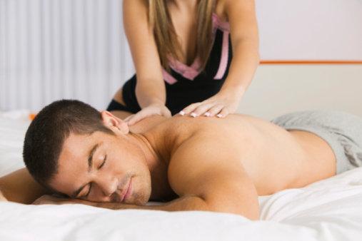 mulher fazendo massagem no homem na cama