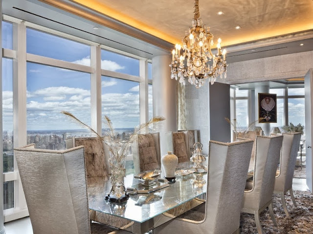 Formal dining room with city view, crystal chandelier, mirrored table and high backed armchairs with nail head trim