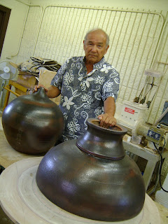 Kauai CC professor Wayne Miyata stands holding sacred ball sections created for Hall of Compassion