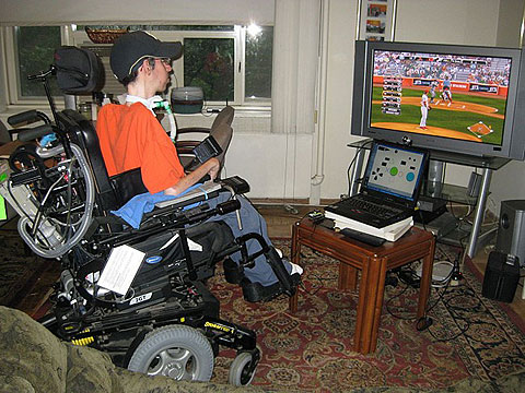 Photo of a man in an electric wheelchair, playing a baseball PS3 game, using just his head-movements and the press of a single button.