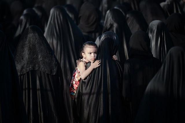 Бахрейн. Мать держит девочку на похоронах Сайеда Хамида Oмрана Сайеда, участника протеста в деревне Карзаккан