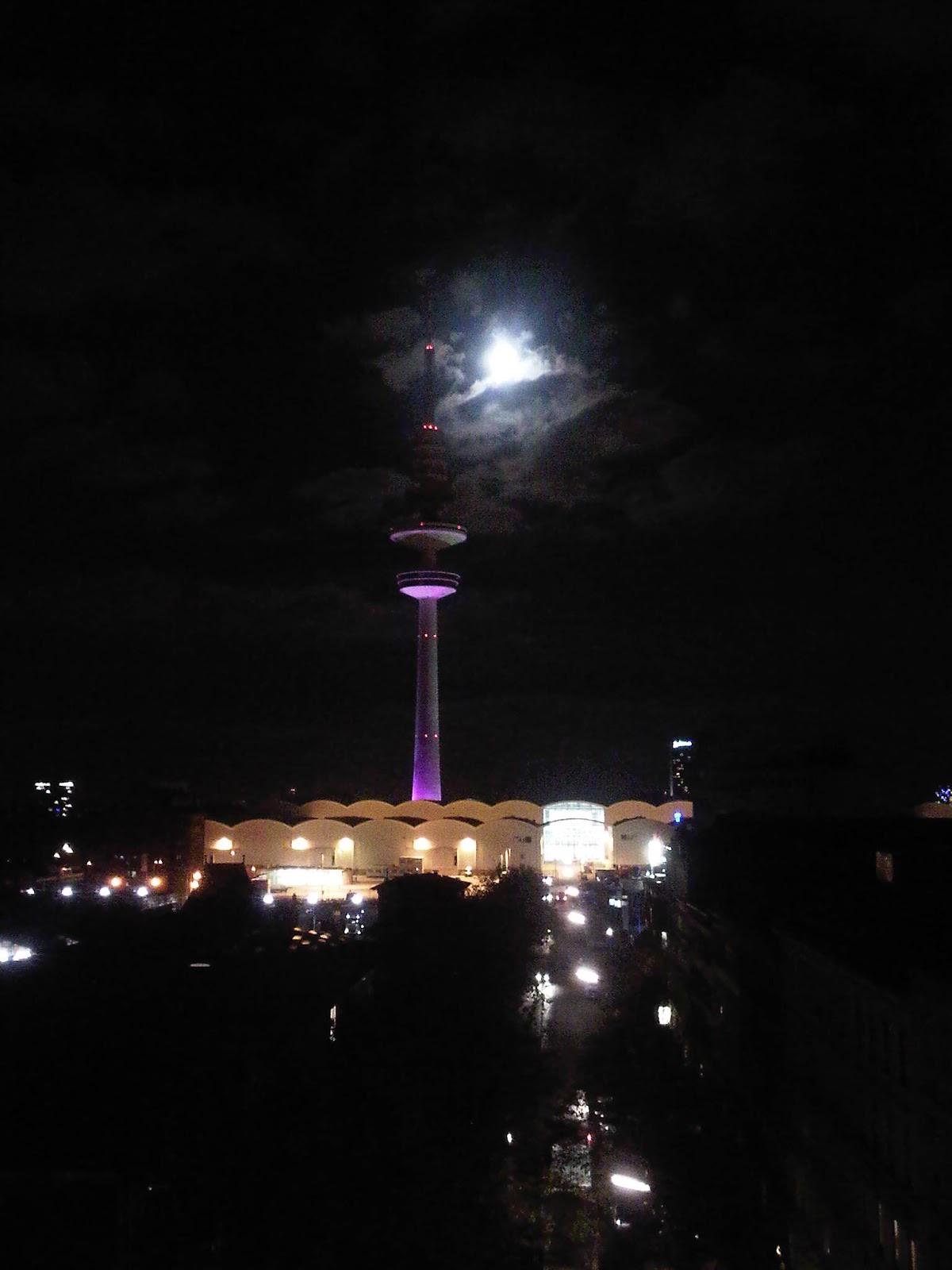 Fernsehturm und Messehallen mit Mond von Wolken halb verdeckt